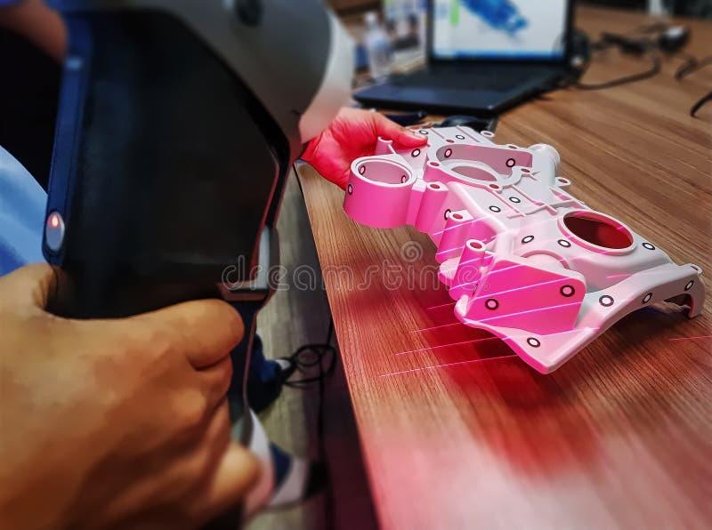 Uomo che per mezzo dell'analizzatore portatile per esplorare il modello di 3D cad della parte meccanica complessa immagini stock libere da diritti