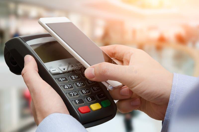 Uomo che per mezzo della macchina di pagamento con carta di credito immagini stock libere da diritti
