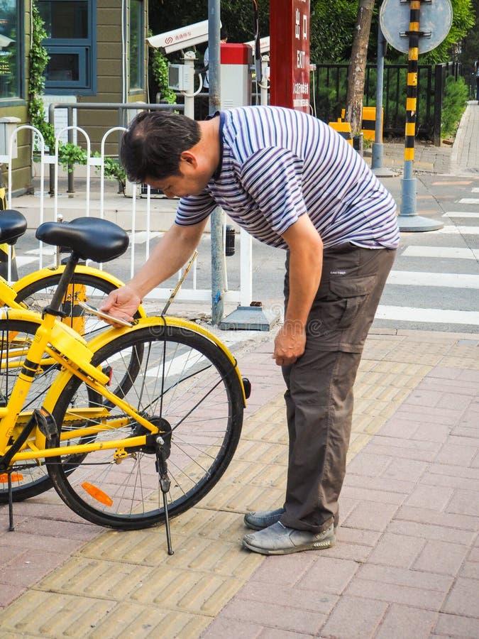 Uomo che per mezzo dello smartphone per esplorare e sbloccare una bici fotografie stock libere da diritti