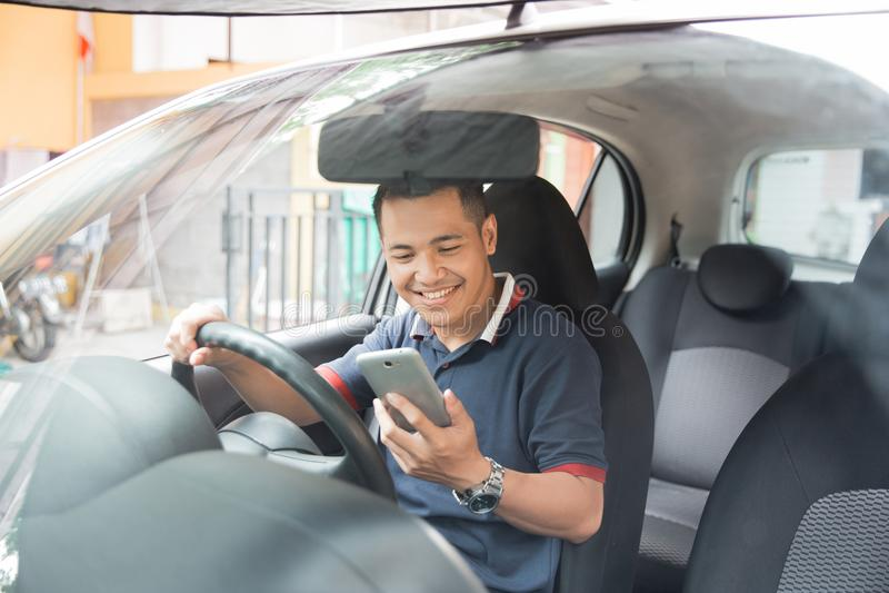 Uomo che per mezzo dello smartphone mentre conducendo un'automobile fotografie stock libere da diritti