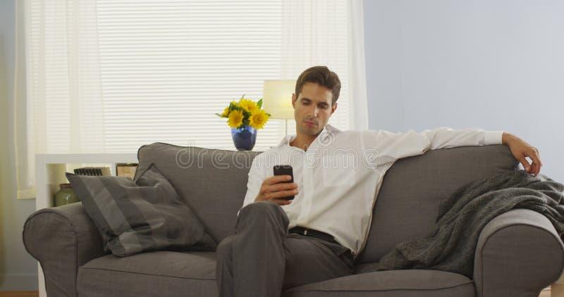 Uomo che per mezzo dello smartphone sullo strato dopo il lavoro immagini stock libere da diritti