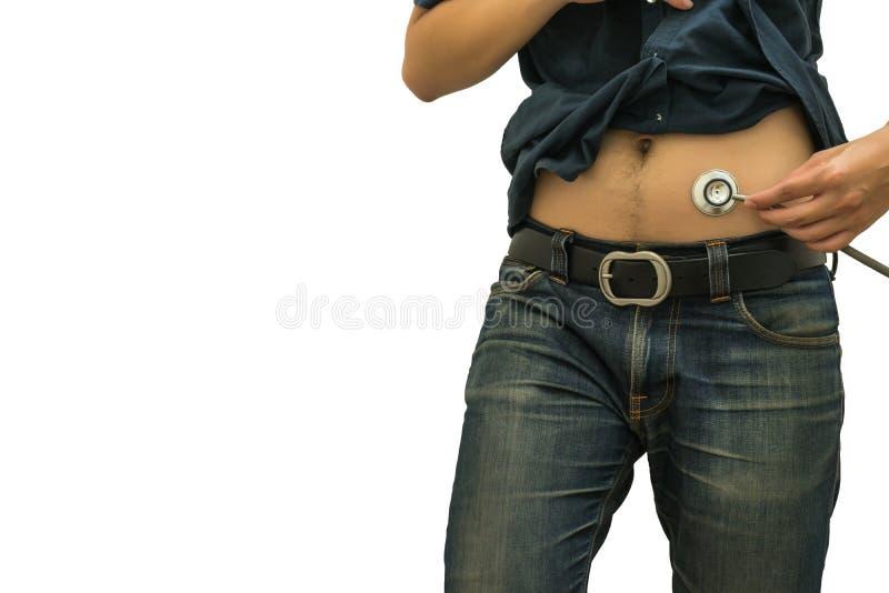 Uomo che per mezzo dello STETOSCOPIO sul fondo di bianco dello stomaco immagini stock libere da diritti