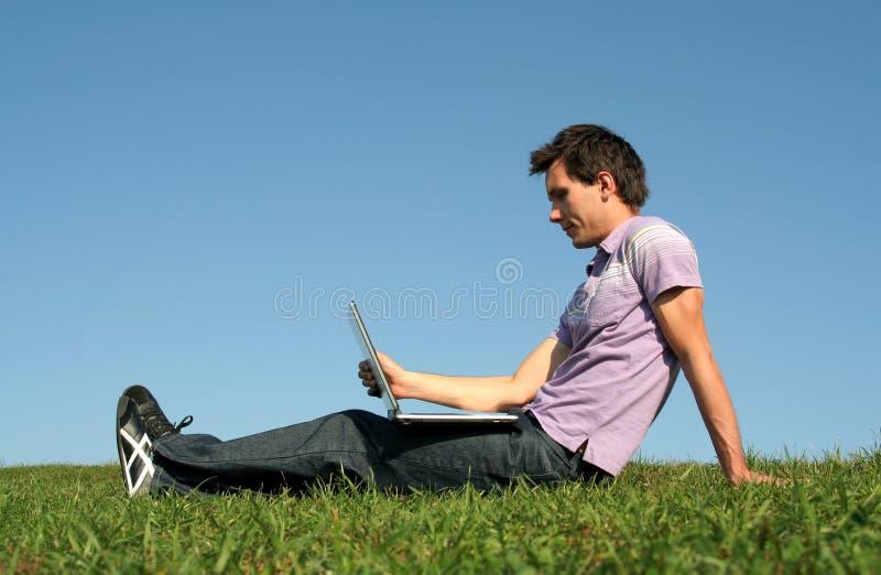 Uomo che per mezzo di un computer portatile all'aperto immagine stock