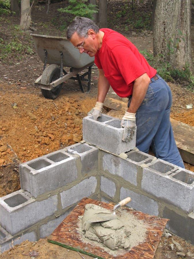 Uomo che pone la parete del blocco in calcestruzzo fotografie stock libere da diritti