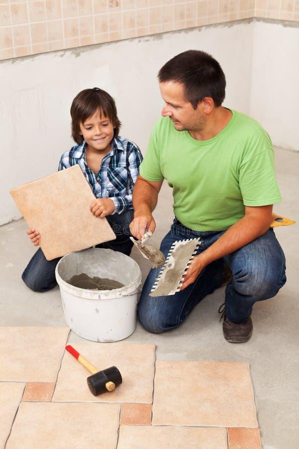Uomo che pone le piastrelle per pavimento ceramiche aiutate dal bambino piccolo immagine stock libera da diritti