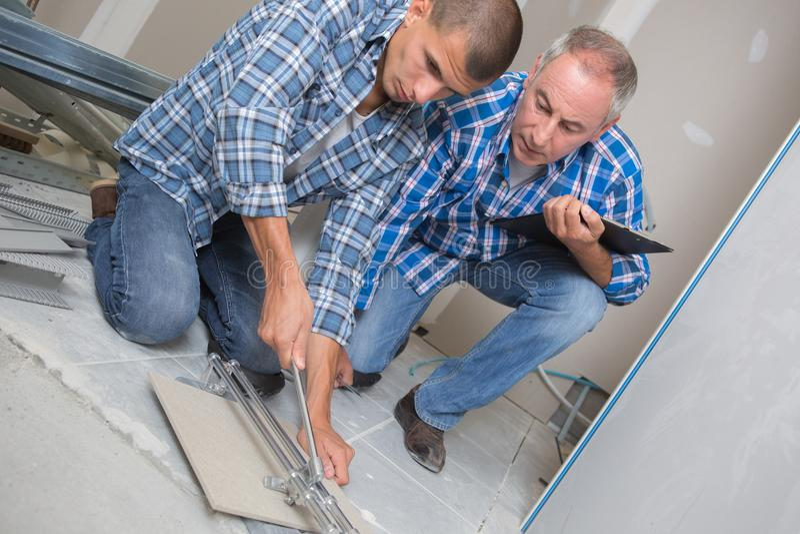Uomo che pone le piastrelle per pavimento ceramiche in nuova costruzione fotografie stock