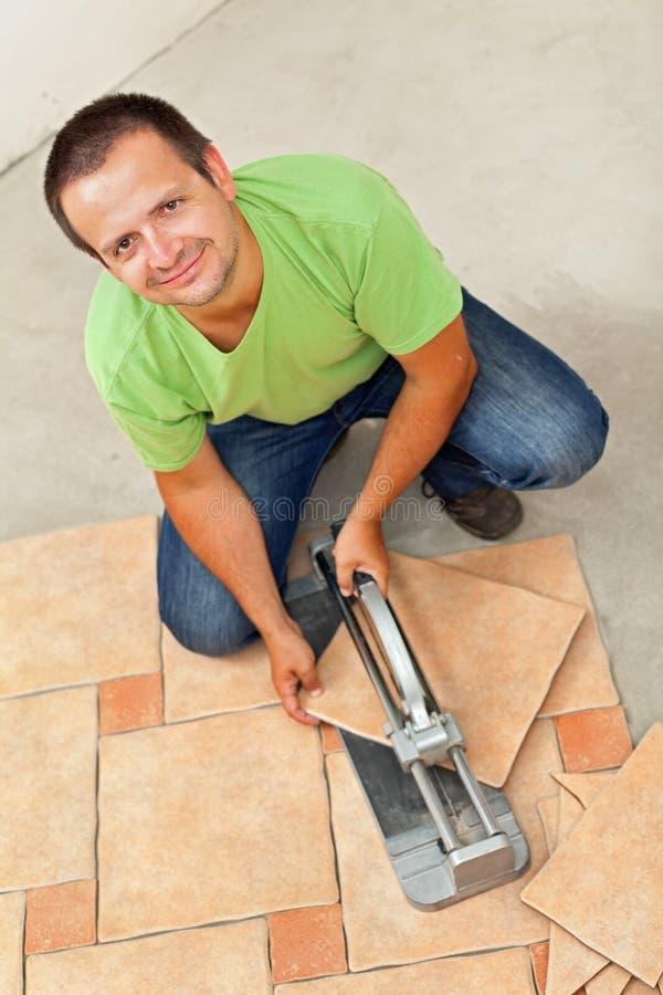 Uomo che pone le piastrelle per pavimento ceramiche - un pezzo solo di taglio immagini stock