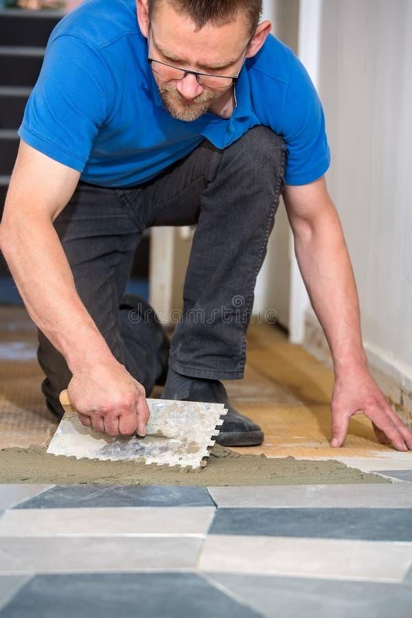 Uomo che pone le piastrelle per pavimento con la cazzuola della piastrellatura fotografie stock libere da diritti