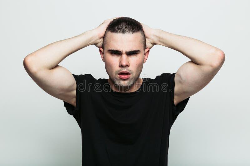 Uomo che posa con le armi sulla testa fotografia stock