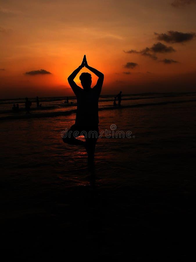 Uomo che posa nella posa di yoga di Vriksha Asana sulla spiaggia del mare durante l'alba fotografie stock libere da diritti