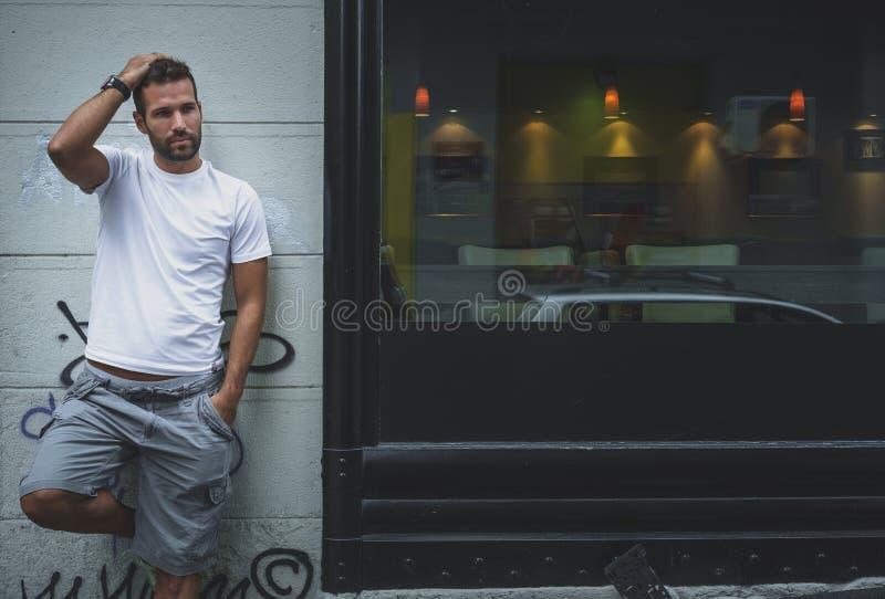 Uomo che posa su una parete fotografie stock