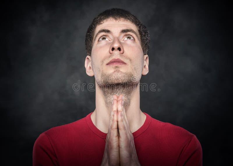 Uomo che prega con le mani afferrate immagini stock libere da diritti