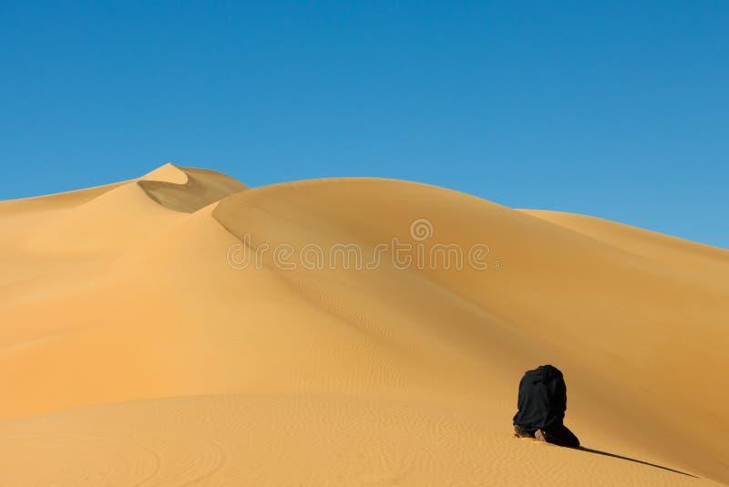 Uomo che prega nel deserto di Sahara, Libia fotografie stock