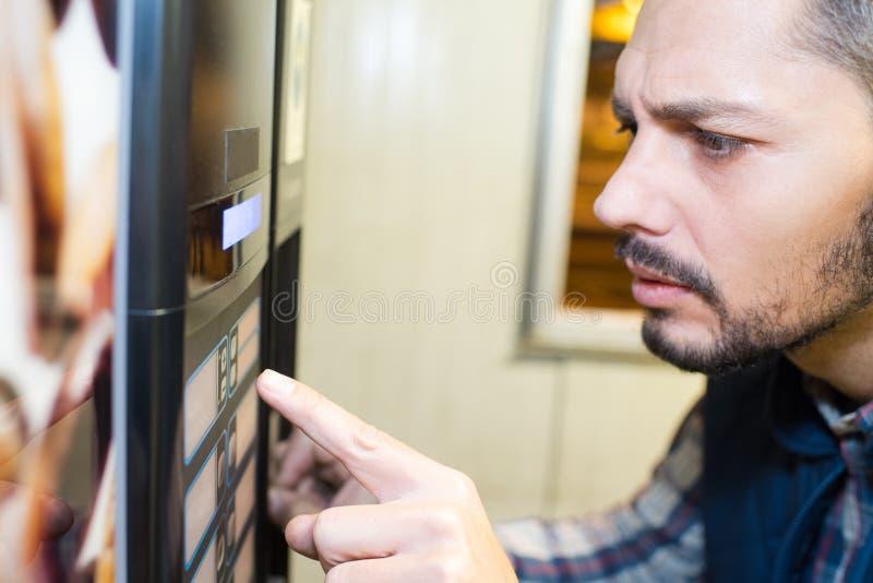 Uomo che preme il distributore automatico fotografie stock libere da diritti