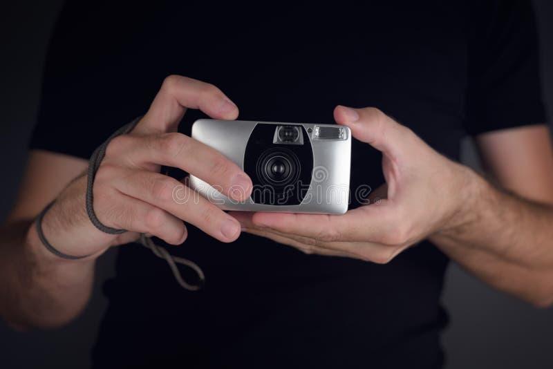 Uomo che prende immagine con la macchina da presa d'annata immagine stock