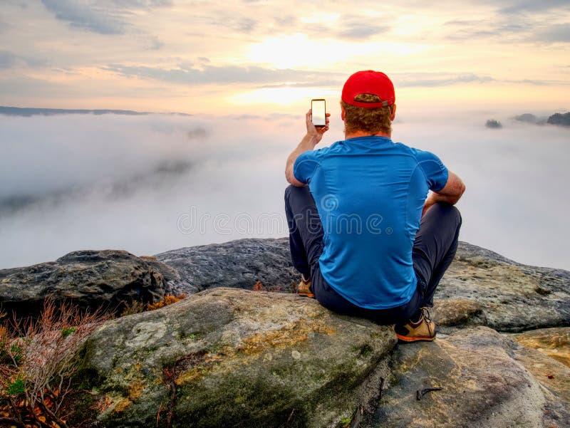 Uomo che prende immagine delle montagne di stupore di caduta sul suo telefono fotografia stock