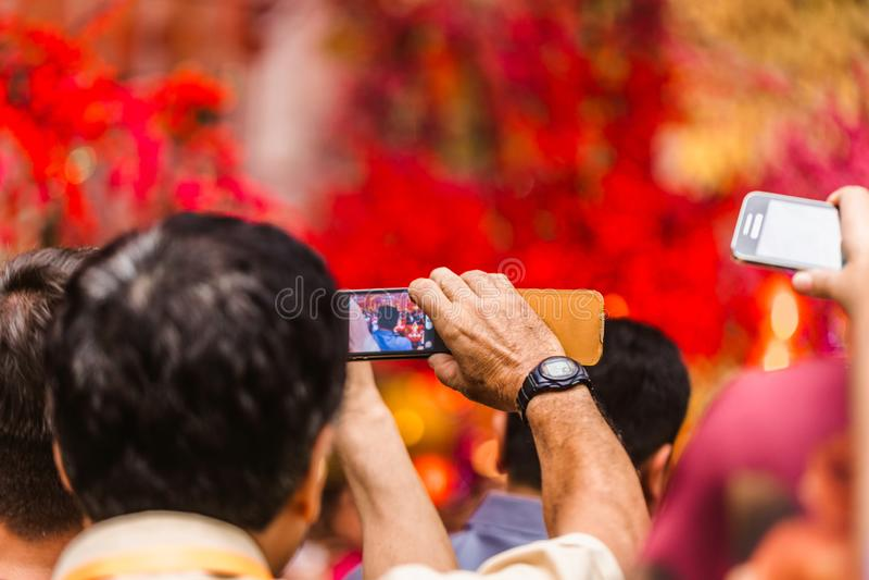 Uomo che prende le immagini sui suoi artisti di prestazione del telefono Nuovo anno cinese fotografie stock libere da diritti