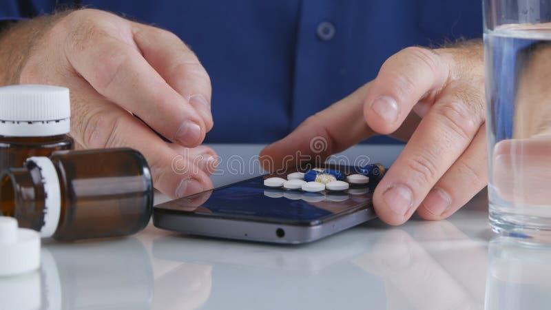 Uomo che prende le pillole variopinte dalla superficie dello schermo del cellulare fotografie stock