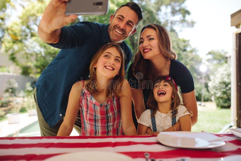 Uomo che prende un selfie della sua famiglia immagini stock libere da diritti