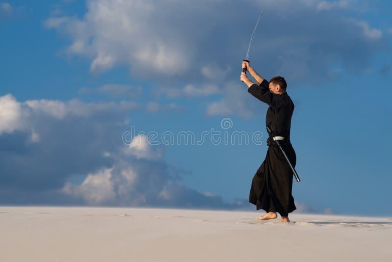 Uomo che prepara le arti marziali giapponesi in deserto fotografia stock