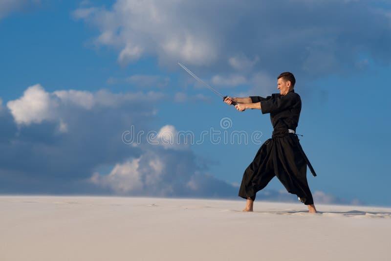 Uomo che prepara le arti marziali giapponesi in deserto fotografia stock libera da diritti