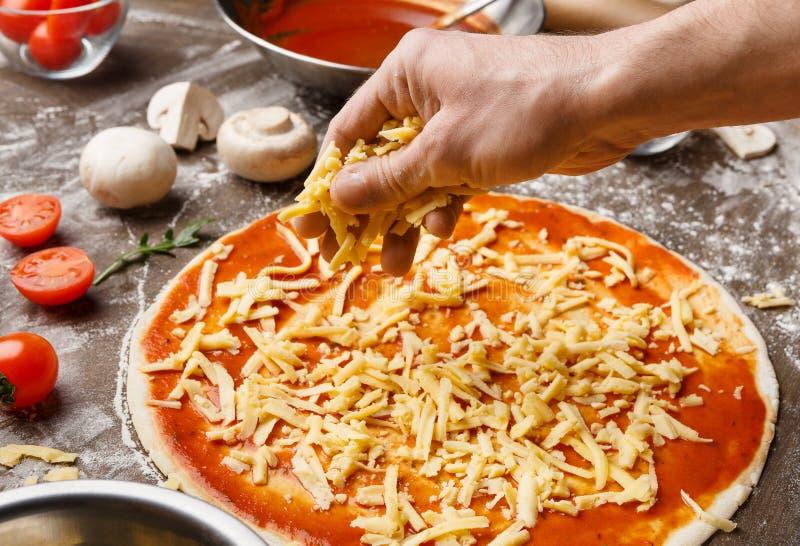 Uomo che produce la pizza, aggiungente formaggio sulla base della pizza immagini stock