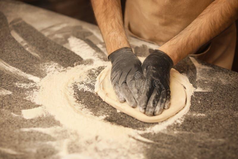 Uomo che produce pizza alla tavola immagine stock libera da diritti