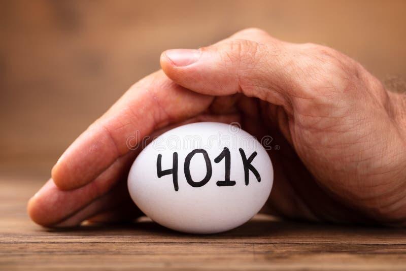 Uomo che protegge uovo bianco 401k fotografia stock