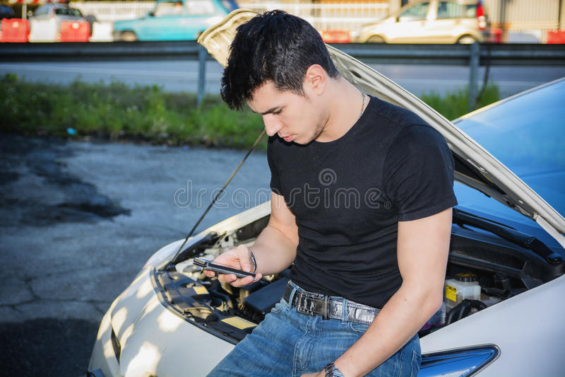Uomo che prova a riparare automobile ed aiuto di ricerca sul telefono fotografia stock libera da diritti