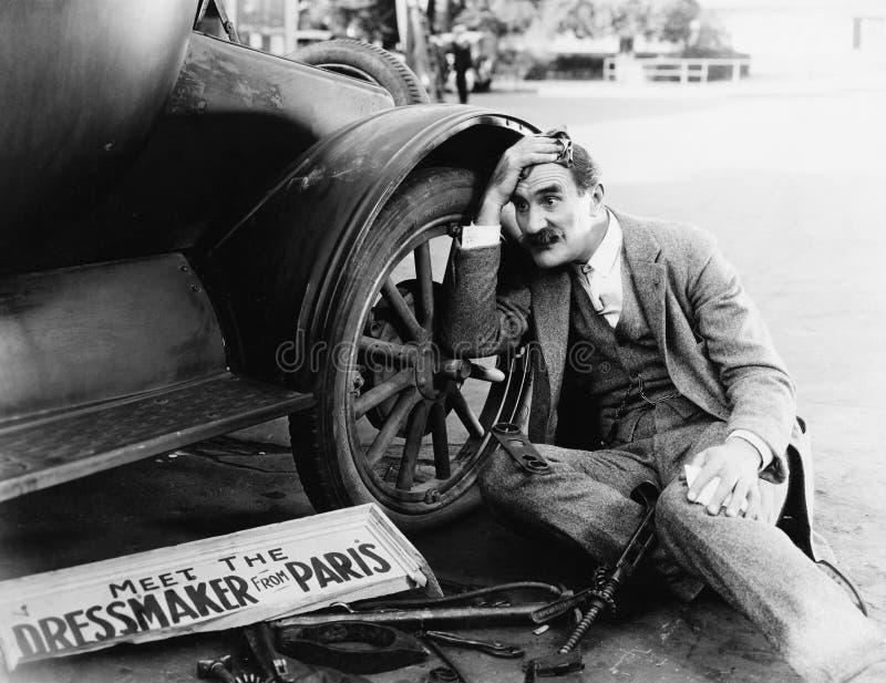 Uomo che prova a riparare automobile tagliata fotografia stock libera da diritti