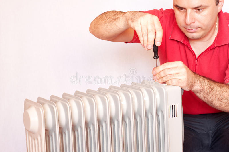 Uomo che prova a riparare un radiatore fotografia stock libera da diritti
