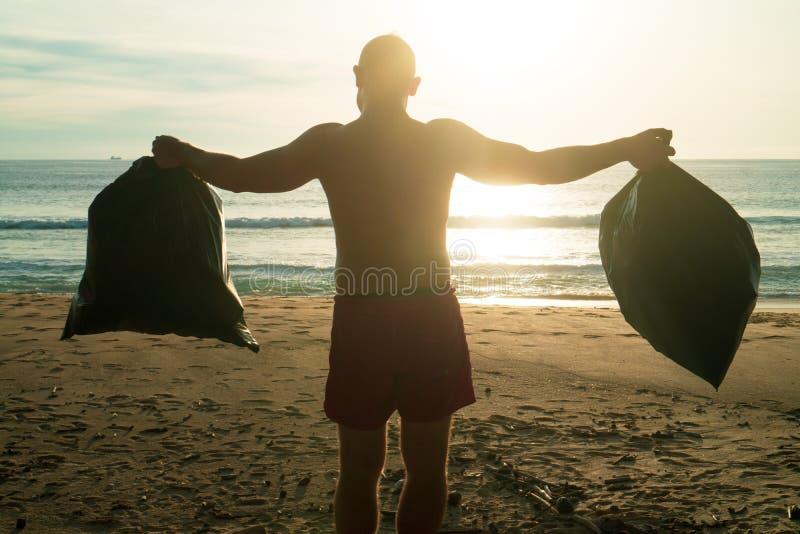 Uomo che pulisce la spiaggia immagine stock