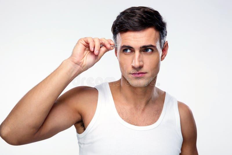 Uomo che rimuove i capelli del sopracciglio con depilare immagine stock