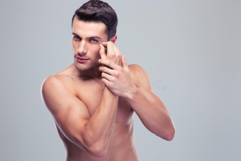 Uomo che rimuove i capelli del sopracciglio con depilare fotografia stock libera da diritti