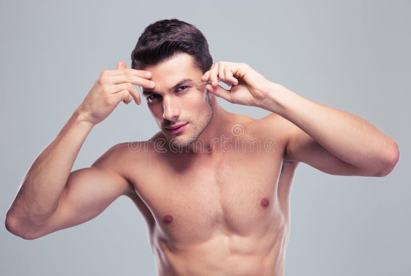 Uomo che rimuove i capelli del sopracciglio con depilare fotografia stock