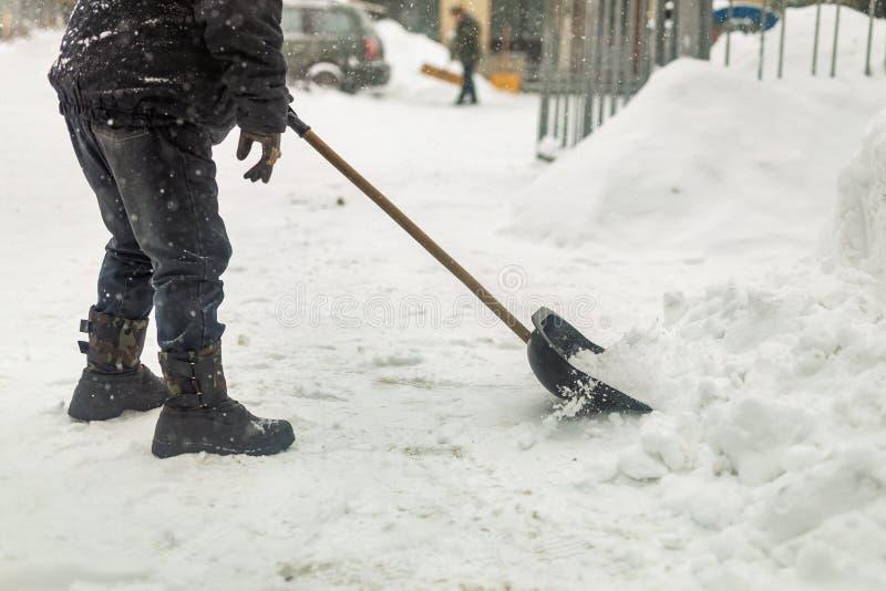Uomo che rimuove neve dal marciapiede dopo le precipitazioni nevose pesanti Conseguenze della bufera di neve e della bufera di ne fotografie stock