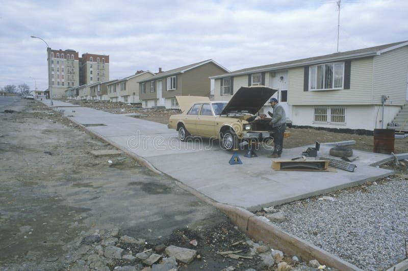Uomo che ripara automobile in quartiere povero, fotografia stock libera da diritti