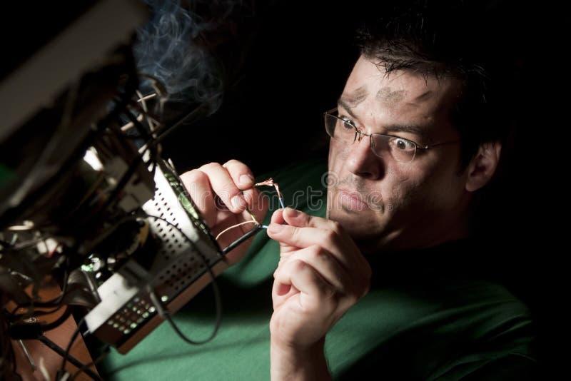 Uomo che ripara computer su fuoco immagine stock libera da diritti
