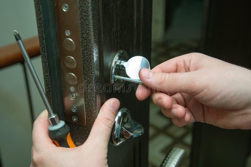 Uomo che ripara la porta con il cacciavite Riparazione della serratura di porta immagini stock