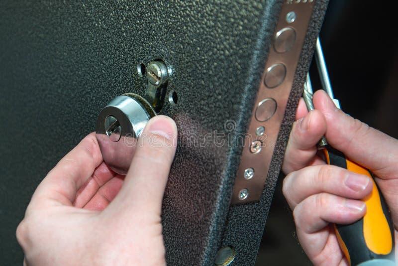 Uomo che ripara la porta con il cacciavite Riparazione della serratura di porta immagine stock