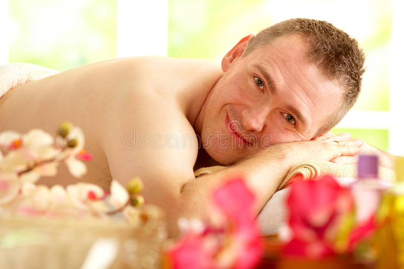Uomo che riposa nel salone della stazione termale fotografia stock