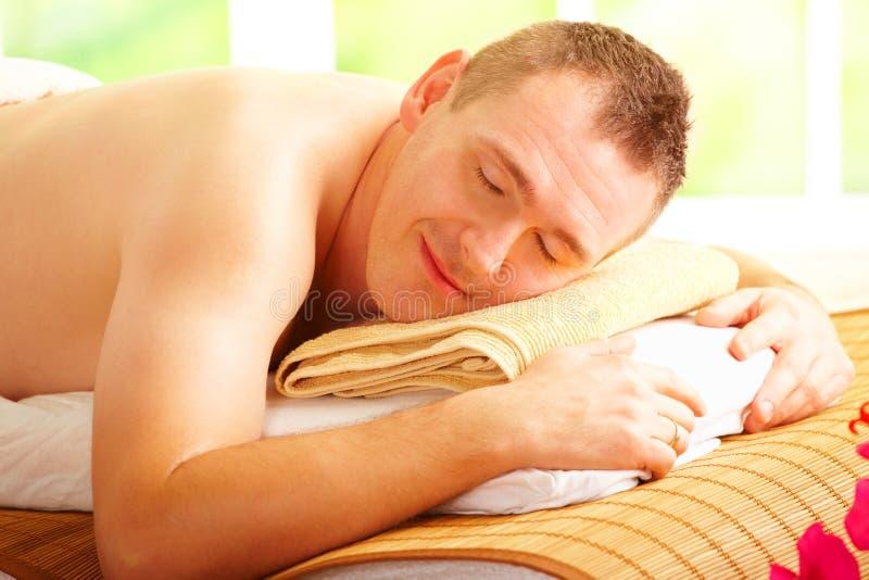 Uomo che riposa nel salone della stazione termale immagini stock