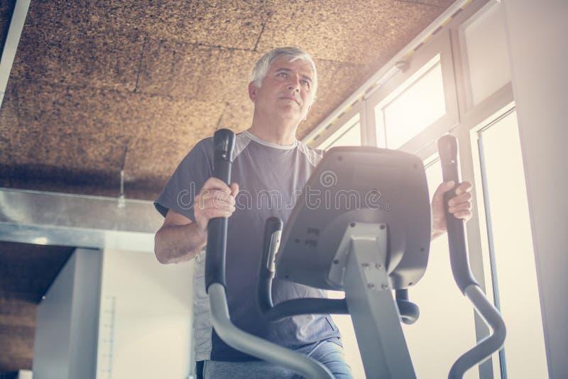 Uomo che risolve sulla macchina ellittica Lavoro dell'uomo senior immagine stock libera da diritti