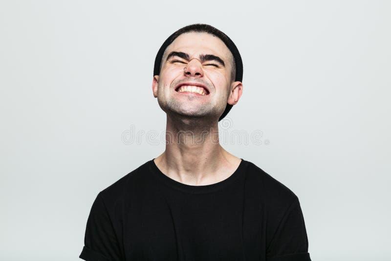 Uomo che ritiene dolore squisito mentre ghignando immagini stock