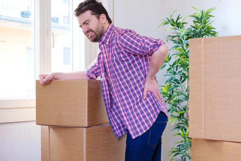 Uomo che ritiene il crampo di dolore posteriore muovere le scatole pesanti immagini stock
