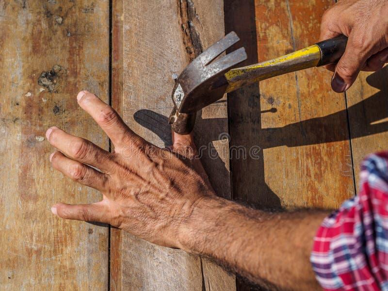Uomo che ritiene la sua mano irritata dopo avere ferita egli stesso mentre martello fotografia stock libera da diritti