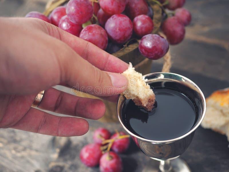 Uomo che rompe il pane, con vino, l'uva e la bibbia nei precedenti immagine stock
