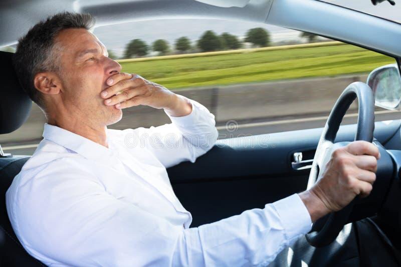 Uomo che sbadiglia mentre conducendo automobile fotografie stock libere da diritti
