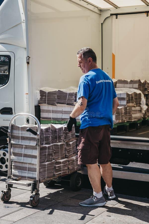 Uomo che scarica il giornale dell'Evening Standard da un furgone a Richmond, fotografia stock libera da diritti