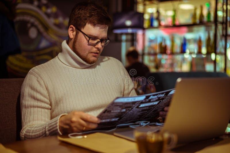 Uomo che sceglie alimento in caffè fotografia stock